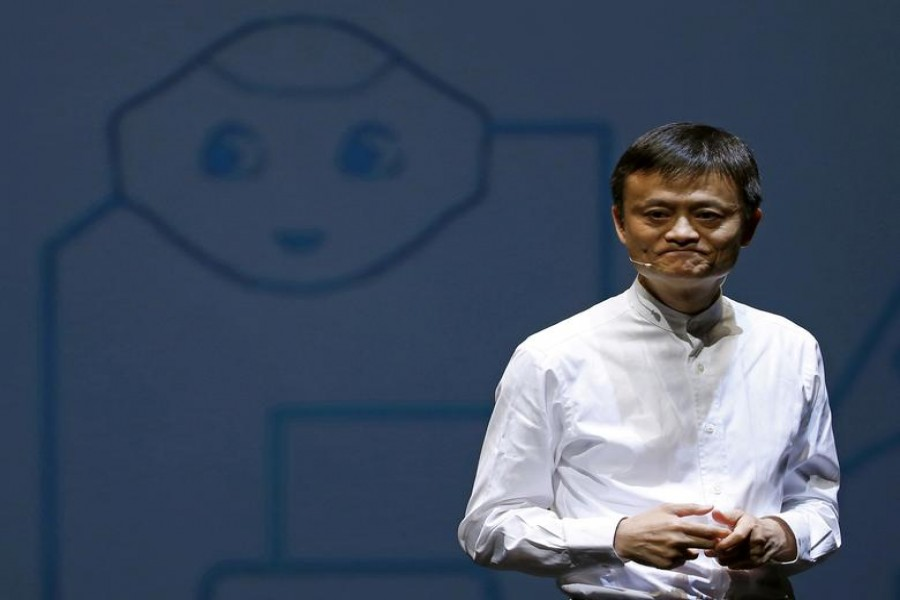 Jack Ma, founder and executive chairman of China's Alibaba Group, speaks in front of a picture of SoftBank's human-like robot named 'pepper' during a news conference in Chiba, Japan, June 18, 2015. REUTERS/Yuya Shino/File Photo/File Photo