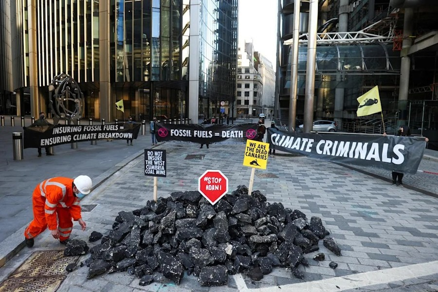 Activists from Extinction Rebellion, a global environmental movement, hold banners as they stand next to fake coal, made from rocks, during a protest outside the Lloyd's building in London — Reuters photo