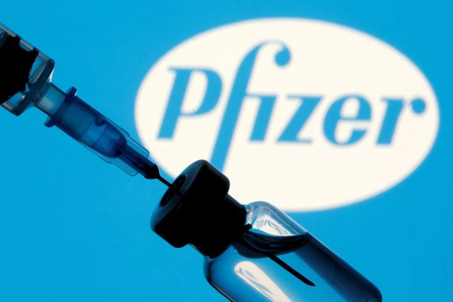 A vial and syringe are seen in front of a displayed Pfizer logo in this illustration taken on January 11, 2021 — Reuters/Files