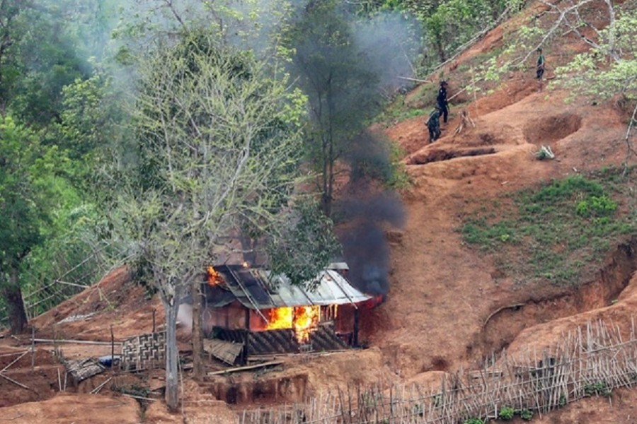 Ethnic minority Karen troops are seen after setting fire to a building inside a Myanmar army outpost near the Thai border, which is seen from the Thai side on the Thanlwin, also known as Salween, riverbank in Mae Hong Son province, Thailand, April 28, 2021. Reuters
