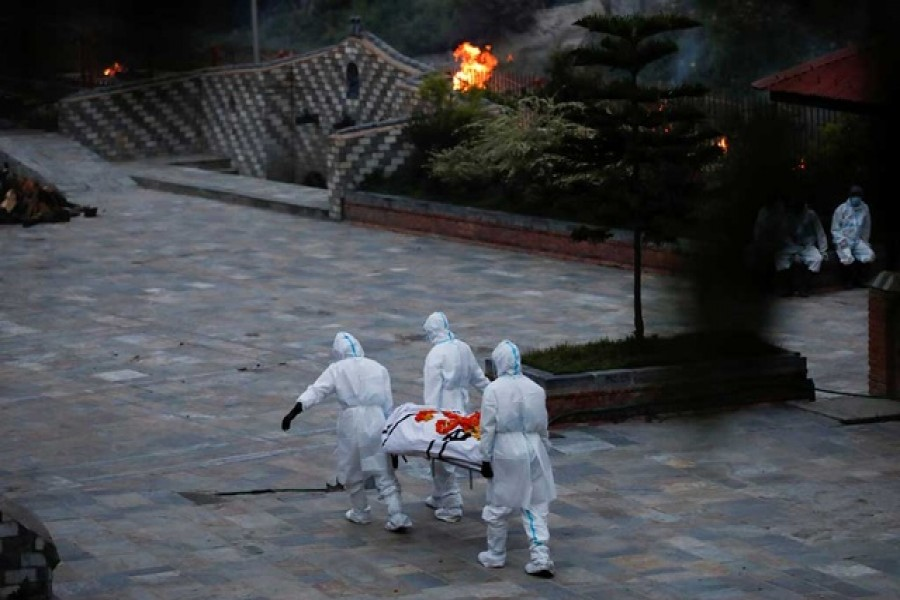 Men wearing personal protective equipment (PPE) carry a body of a coronavirus disease (COVID-19) victim at the crematorium as the country recorded the highest daily increase in deaths since the pandemic began, in Kathmandu, Nepal May 3, 2021 - Reuters photo