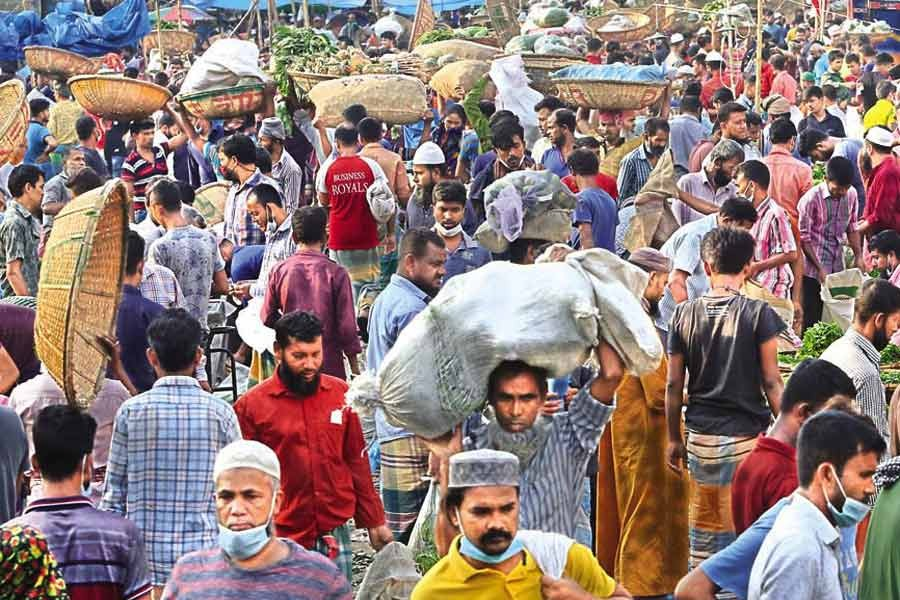 Sellers and buyers going about their business at Karwan Bazar kitchen market in the city on Tuesday, paying no heed to mask mandate or social distancing norms —FE photo by KAZ Sumon