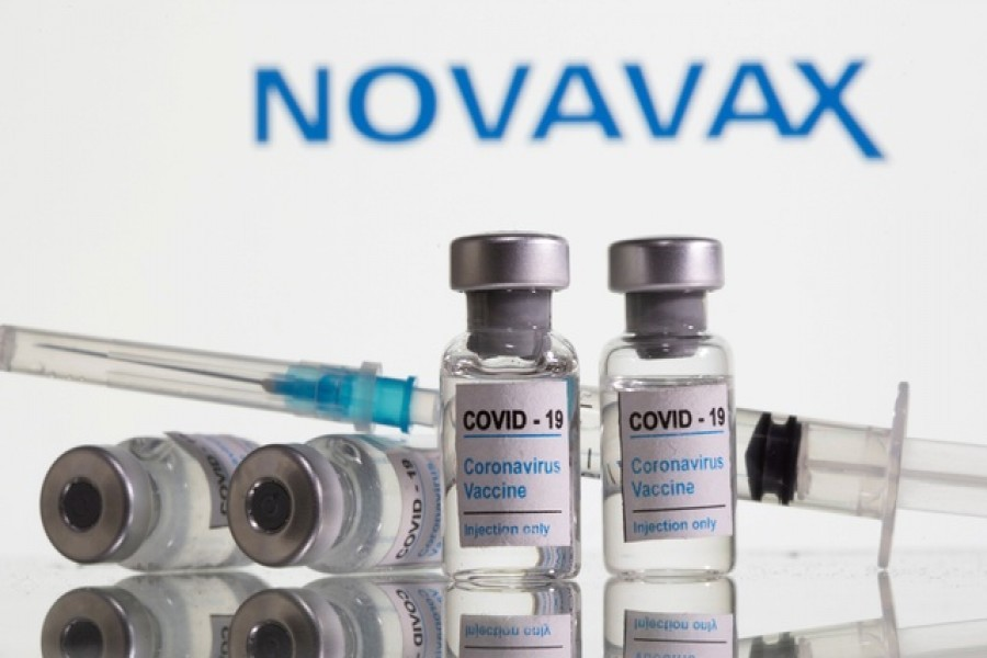 """Vials with a sticker reading, """"COVID-19 / Coronavirus vaccine / Injection only"""" and a medical syringe are seen in front of a displayed Novavax logo in this illustration taken October 31, 2020. REUTERS"""