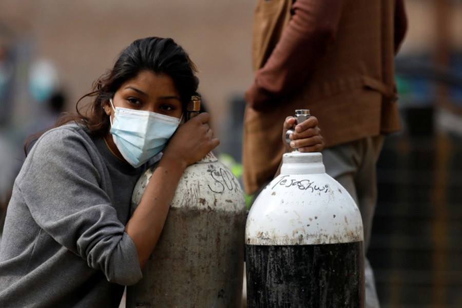 A woman holds on to the oxygen cylinders for a patient after refiling them at a factory, amidst the spread of coronavirus disease (Covid-19) surge as India's outbreak spreads across South Asia, in Kathmandu, Nepal on May 9, 2021 — Reuters photo