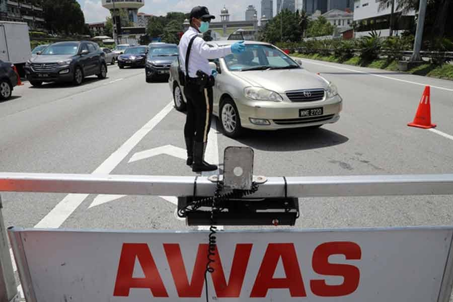 A police officer standing guard at a roadblock during lockdown ahead of the Eid al-Fitr celebrations in an effort to prevent a large-scale transmission of the coronavirus disease (COVID-19), in Petaling Jaya, Malaysia, on Monday -Reuters photo