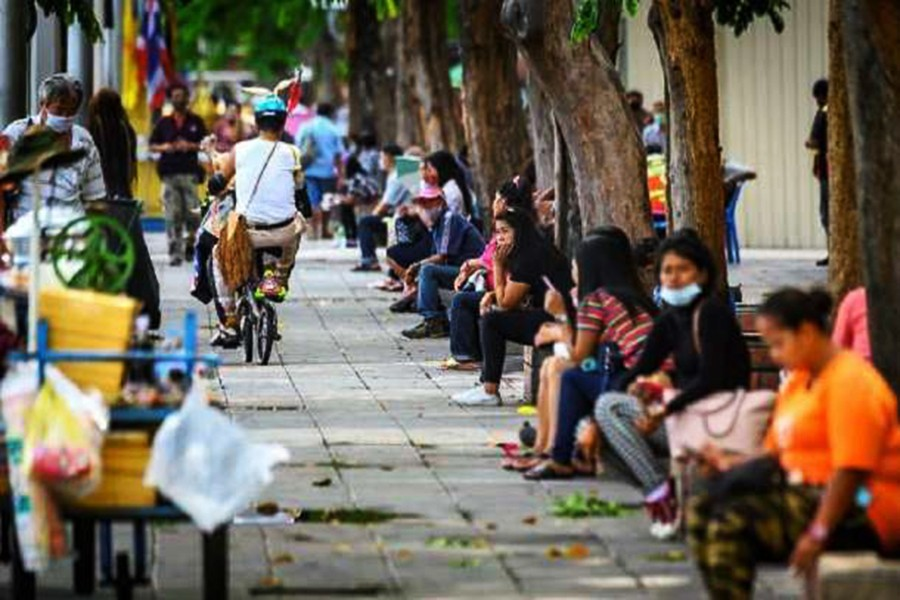 Unemployed people sit on the side of a road in Bangkok on Sept. 15. Thailand's economy has been impacted severely by the Covid-19 pandemic.