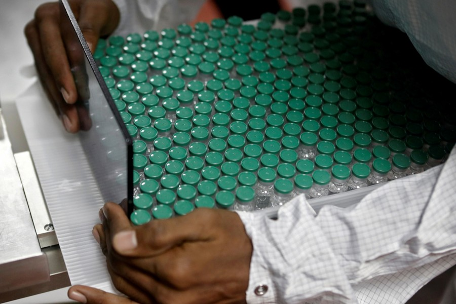 An employee in personal protective equipment (PPE) removes vials of AstraZeneca's COVISHIELD, coronavirus disease (Covid-19) vaccine from a visual inspection machine inside a lab at Serum Institute of India, in Pune, India on November 30, 2020 — Reuters/Files