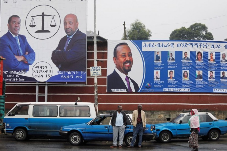 Taxi drivers stand in front of campaign banners of the Ethiopian Prime Minister Abiy Ahmed, and Birhanu Nega, head of the Ethiopian Citizens for Social Justice party, hours before Ethiopia's parliamentary and regional elections, in Addis Ababa, Ethiopia on June 20, 2021 — Reuters photo