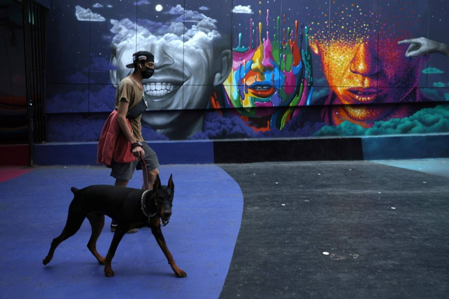 A man walks a dog as lockdown restrictions increase during the coronavirus disease (COVID-19) outbreak, in Santiago, Chile on March 31, 2021 — Reuters/Files