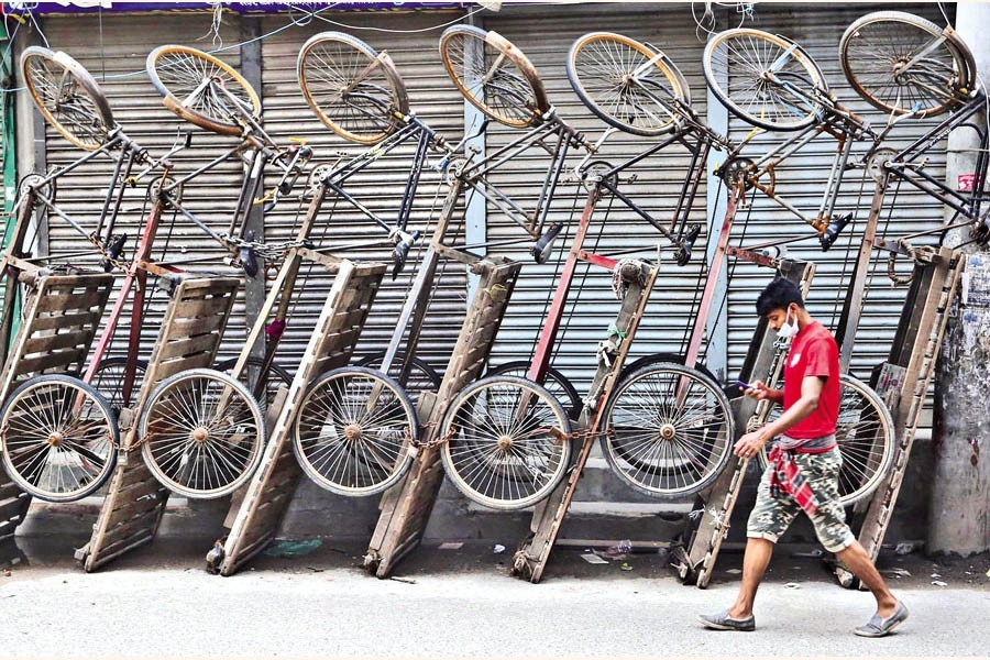 Rickshaw-vans, which are meant for carrying goods, now lying idle by the roadside in Bangshal area of the city. With shops and businesses remaining shut during the lockdown, the income of the van drivers has come down to zero. The photo was taken on Monday — FE photo by KAZ Sumon