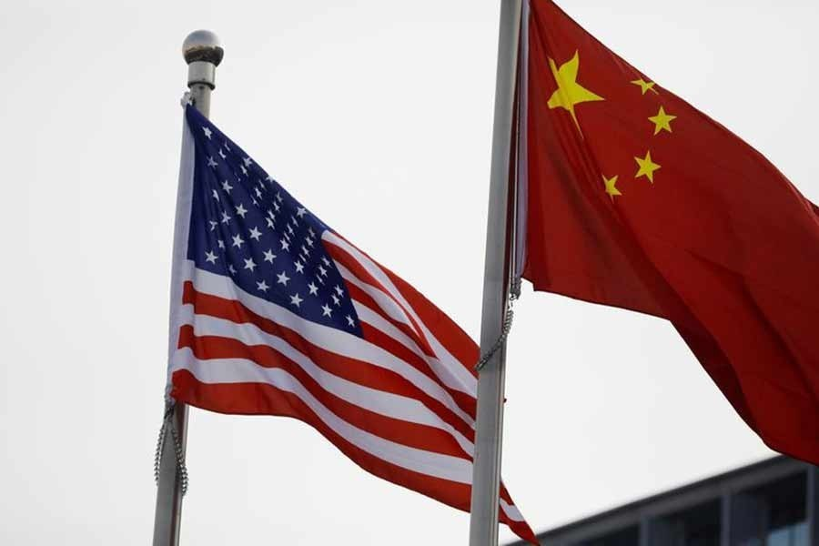 Chinese and US flags flutter outside a building — Reuters/Files