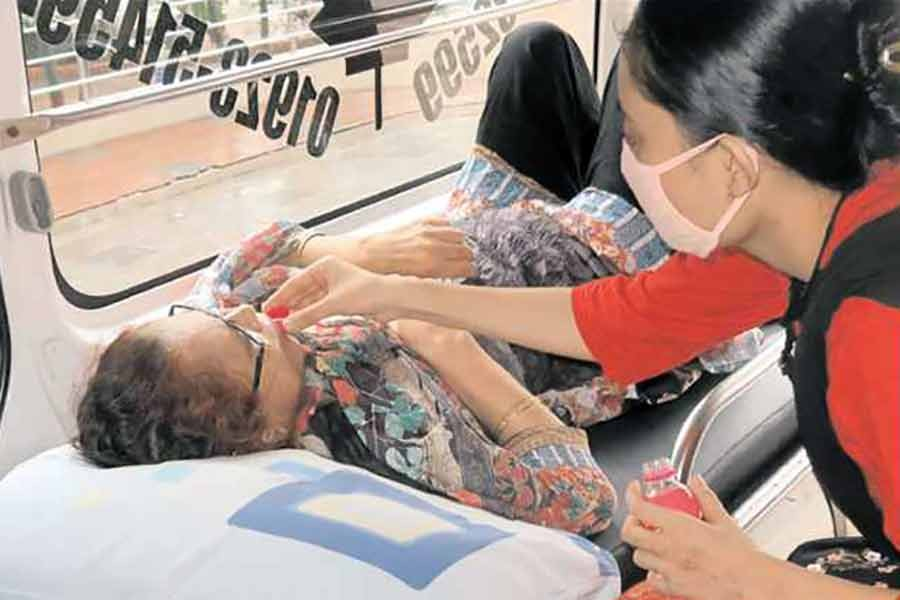 A girl giving a sip of water to her Covid-19 positive mother in an ambulance, moment after she reached Dhaka Medical College Hospital to get admitted there for better treatment. The scene was photographed on Friday —FE photo