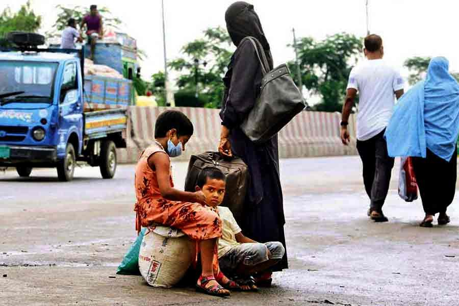 A woman, along with two children, is waiting for a vehicle at Gabtoli in Dhaka on Monday. They somehow managed to reach the outskirt of Dhaka during suspension of long-haul transportation services amid the Covid-induced lockdown, but found it difficult to get a vehicle to ferry them inside the city —FE photo by KAZ Sumon