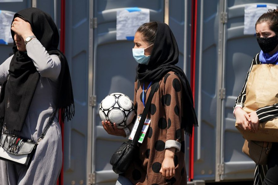 An Afghan woman holding a soccer ball and wearing a CAFA (Central Asian Football Association) credential, waits in line at a processing centre for refugees evacuated from Afghanistan at the Dulles Expo Center near Dulles International Airport in Chantilly, Virginia, US on August 24, 2021 — Reuters/Files