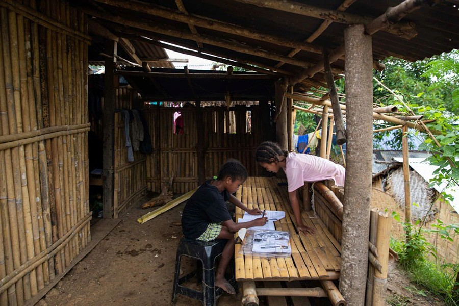 Seventh grade student Ryza Delos Santos, 10, works on her modules at home as her cousin observes, after a session at the makeshift rickshaw distance learning centre for the Aeta community in Porac, Pampanga, Philippines on October 12, 2020 — Reuters