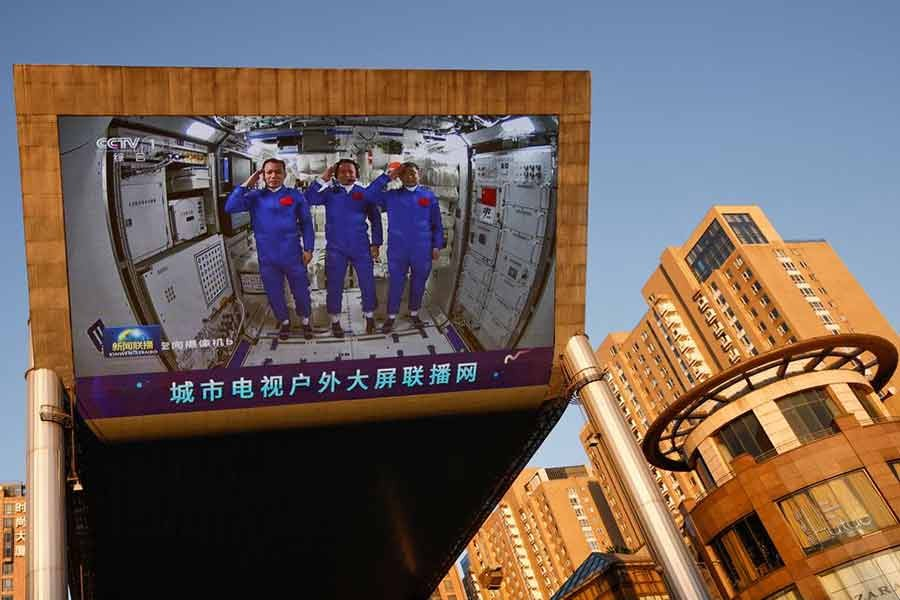 A giant screen at a shopping mall in Beijing on June 18 this year showing Chinese astronauts Nie Haisheng (C), Liu Boming (R), and Tang Hongbo of the Shenzhou-12 mission inside the Tianhe core module of China's space station -Reuters file photo
