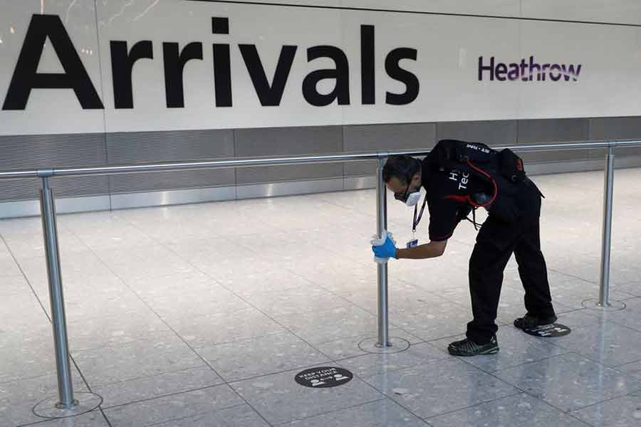 A worker sanitising a barrier at the international arrivals area of London's Heathrow Airport in Britain on August 2 this year -Reuters file photo