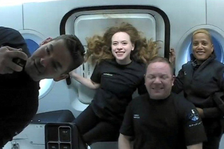 Jared Isaacman, left, and the rest of the team inside the capsule - REUTERS