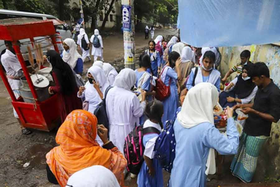 Students crowding a food shop outside Agrani School and College in Dhaka's Azimpur on Wednesday, breaching physical distancing rules amid the coronavirus pandemic –bdnews24.com photo